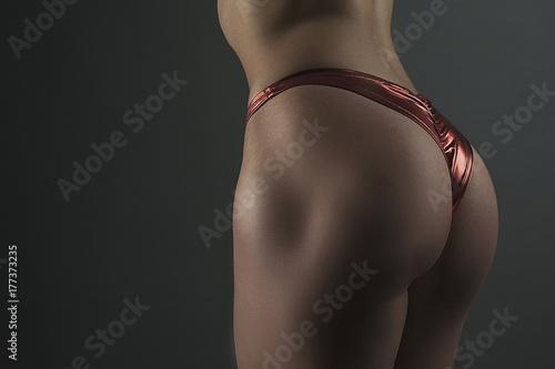 Fototapeta fitness kobieta tyłek na ciemnym bg bliska zdjęcie