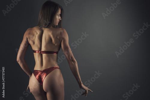 Plakat kobieta fitness powrót bikini sport studio strzał na ciemnym bg