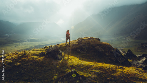 Foto auf Gartenposter Grau Verkehrs Hiker Young Woman With Backpack Rises To The Mountain Top Against Backdrop Of Sunset. Discovery Travel Destination Concept