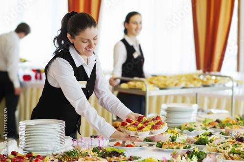 Fototapeta Restaurant waitress serving table with food obraz