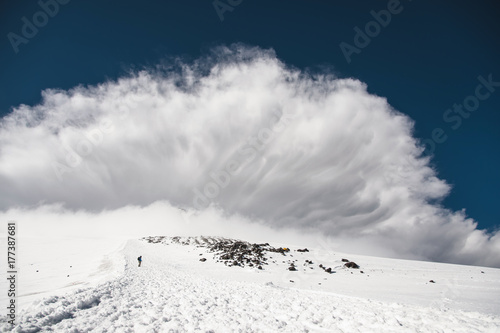 Leinwand Poster Stormy clouds overhang over the snow-capped mountain Elbrus