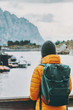 Traveler with backpack enjoying Norway village landscape Travel Lifestyle concept adventure winter vacations outdoor