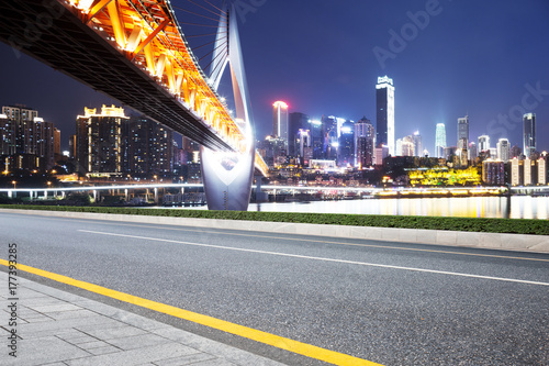 Zdjęcie XXL pusta asfaltowa droga z nowoczesnym mostem i nowoczesnym miastem