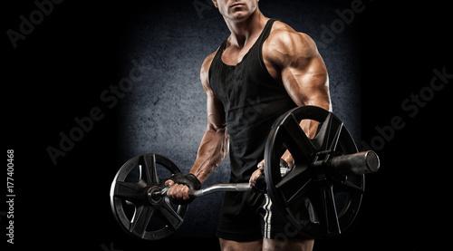 Plakat Młody seksowny bodybuilder z perfect ciałem robi ćwiczeniu z barbell na czarnym tle.