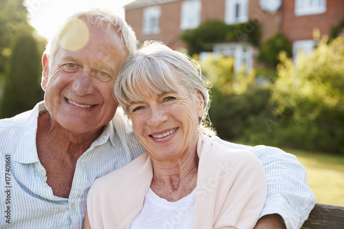 Plakat Starszy pary obsiadanie Na Ogrodowej ławce W wieczór świetle słonecznym