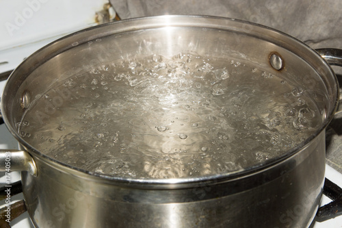 Fotografie, Obraz  Stainless steel pot is on a gas stove and it boils water.
