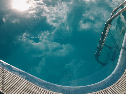 Reflection of the clouds in the water of swimming pool