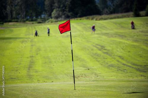 Plakat Czerwona flaga na zielonym golfie z graczami daleko w tle