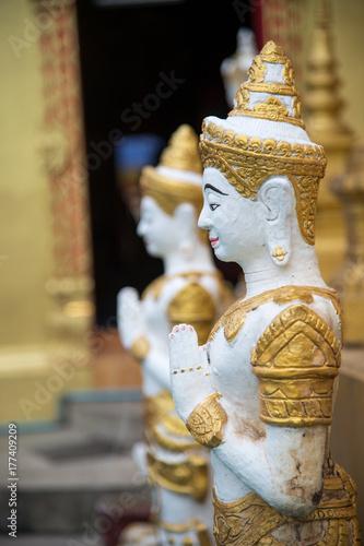 """Plakat piękny posąg pokazuje kulturę tajlandzką w akcji """"Wai"""" lub tajskie powitanie"""