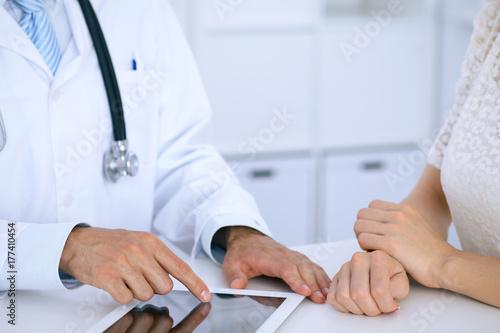 Plakat Doktorski i cierpliwy opowiadać podczas gdy siedzący przy biurkiem w biurze. Lekarz wskazując na komputer touch pad lub tabletu. Medycyna i koncepcja opieki zdrowotnej