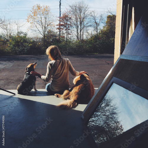 A woman sits on loading dock with two dogs.