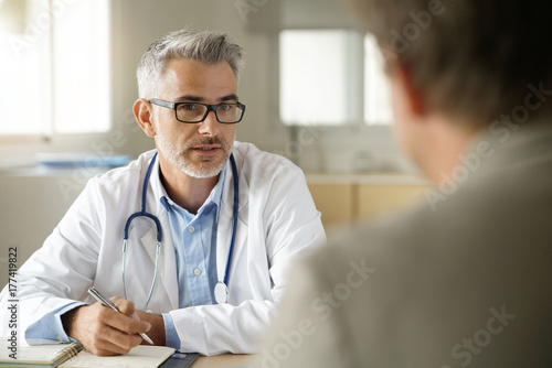 Fotomural Doctor talking to patient in office