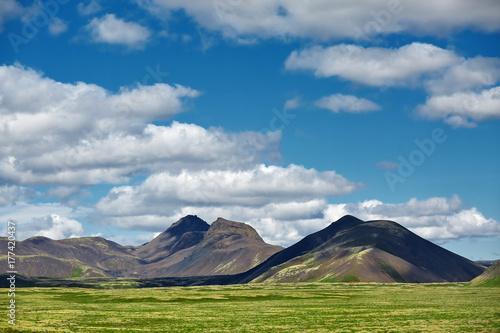 Fototapeta Podróż do Islandii. Piękny Islandzki krajobraz z wulkanem, górami, zielonym mech i niebieskim niebem z białymi chmurami.