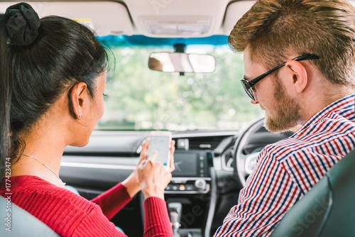 Zdjęcie XXL Wieloetniczny para kochanek, biały człowiek i czarna dziewczyna azjatyckich za pomocą aplikacji systemu nawigatora na inteligentny telefon w samochodzie. Nowoczesny styl życia gadżetów, rodzinne podróże lub koncepcja usługi wezwania taksówek online.