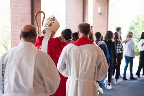 Photo Vescovo che si avvia verso la chiesa con i suoi fedeli per la cresima