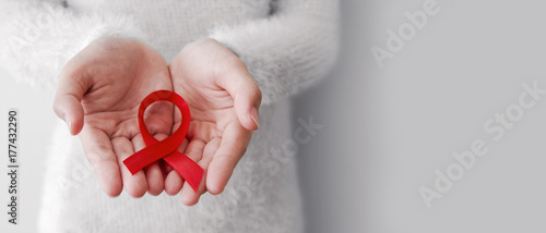 Photo Red ribbon on woman hands for world aids day with copy space