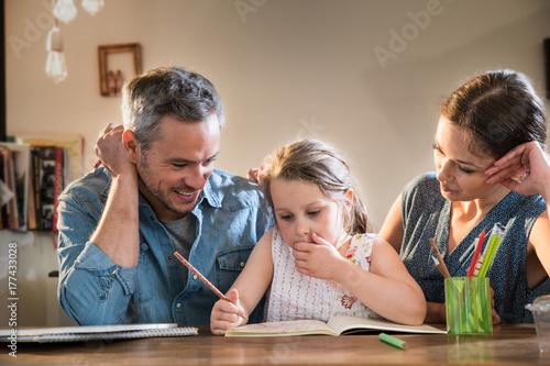 Vászonkép Mom and Dad help their little girl do homework for school
