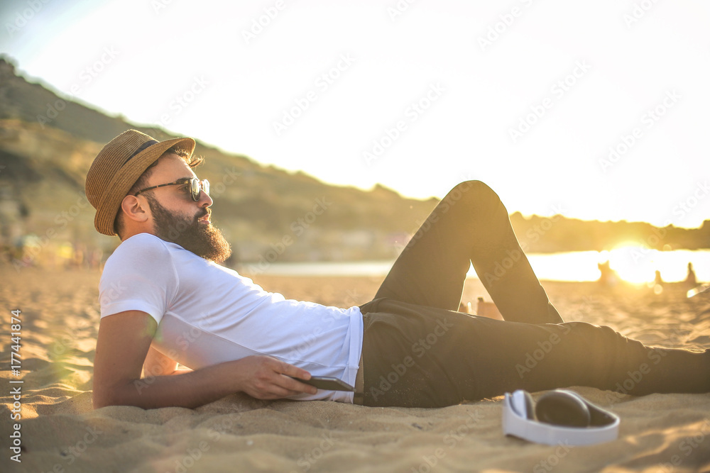 Fototapety, obrazy: Handsome guy lying down at the beach