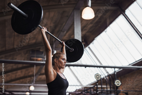 Vászonkép  Fit woman lifting barbells over her head in a gym