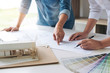 Two interior design or graphic designer at work on project of architecture drawing with work tools and color swatches, colour chart, color samples for selection, renovation and technology concept