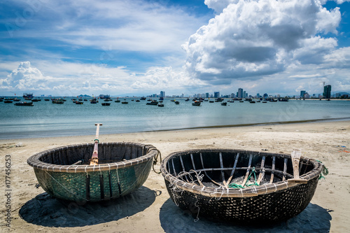 Old fishing boats next to modern skyline in Da Nang Tableau sur Toile