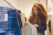 Young Woman In A Store Checking The Price On The Label