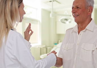 Smiling female doctor giving handshake to senior male patient. Health care concept