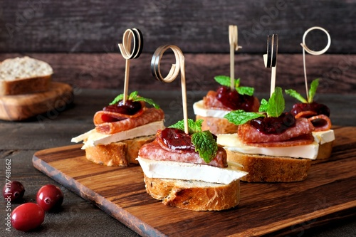 In de dag Voorgerecht Holiday crostini skewers with cranberry sauce, brie, salami, and mint on a wooden server