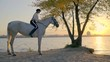 A woman in a white shirt sits riding a white horse on a background of a river at sunset time