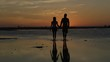 Silhouette of couple holding hands walking on beautiful sandy beach at sunset
