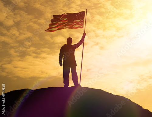Silhouette of man holding US flag American on the mountain Poster