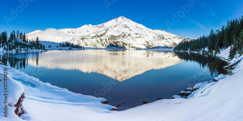 Zdjęcie XXL Pokryty śniegiem szczyt górski znajduje odzwierciedlenie w spokojnych porannych wodach wysokiego jeziora elewacji.
