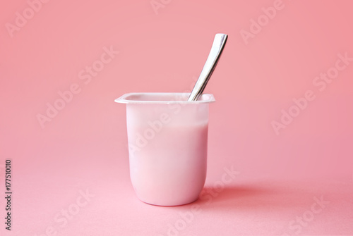 Fototapeta Delicious strawberry yogurt or pudding  in white plastic cup on pink background with copy space. Strawberry pink yoghurt with spoon in it. Minimal style. obraz