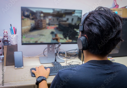 Photo Back view of young gamer playing FPS video games at home