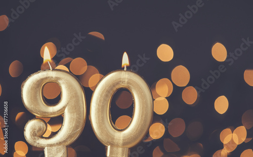 Photo  Gold number 90 celebration candle against blurred light background