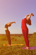 Two young fair-haired girls in sports suits practice yoga on a picturesque green hill in the open air in the evening. The concept of sport exercising outdoors