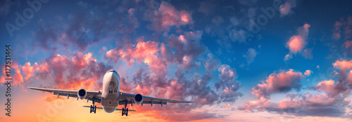 Türaufkleber Flugzeug Airplane and beautiful sky. Landscape with passenger airplane is flying in the blue sky with red, purple and orange clouds at sunrise. Travel. Passenger airliner. Commercial aircraft. Private jet