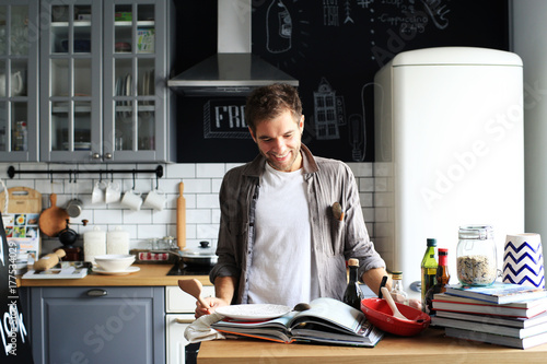 Poster Cuisine Young man cooking lunch in the kitchen