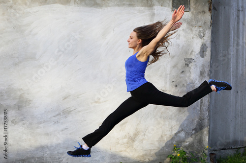 Poster Nautique motorise Healthy jump, gray background, woman jumping sport outdoor, street, looking camera, copy space