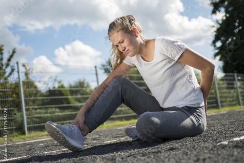 Eine junge Frau hat sich beim Sport am fuss verletzt Canvas Print
