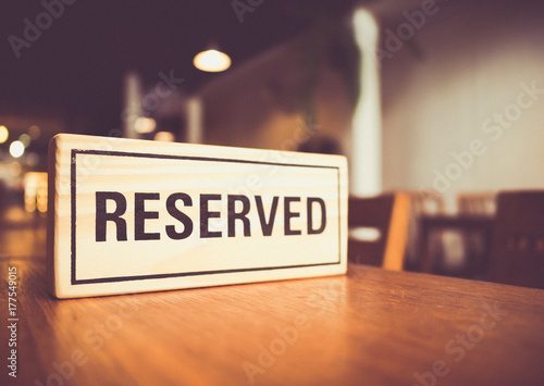 Stampa su Tela wooden reserved sign with capital letters on dining table in restaurant, retro t