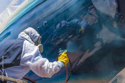 Fotomural spritzlackierer bei der Endlackierung eines Schiffsrumpfes