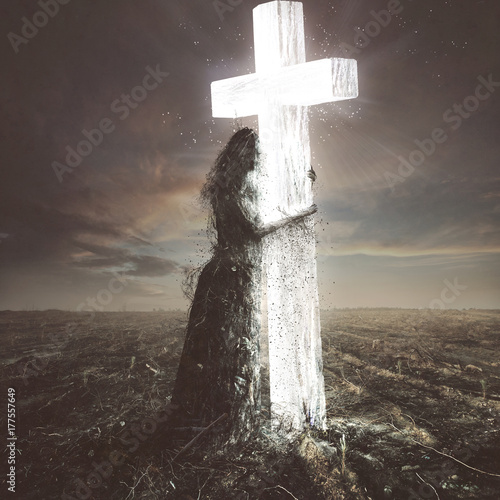 Fotografia Woman made of dirt clings to the cross