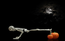 Halloween Skeleton Doing Pushups On A Pumpkin Under A Nice Night Time Moon Covered With Dark Clouds.