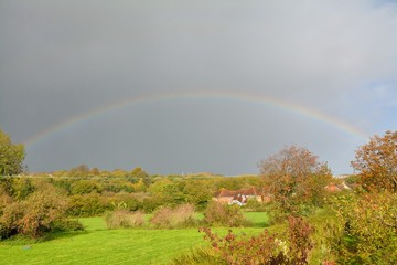 Fading rainbow in gloomy skies during Strom Brian over UK in October 2017