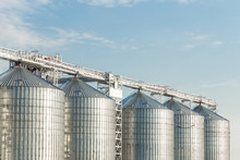 Modern Agricultural Silos Or Grain Elevator With Blue Sky On The Background. Storage Of Grain And Other Different Cereals