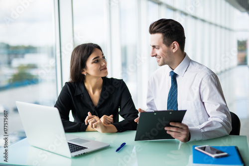 Fotografía  Client signing a document in an office with a businesswoman looking the contract