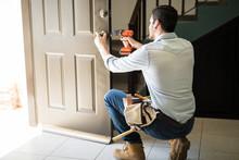 Young Man Fixing A Door Lock