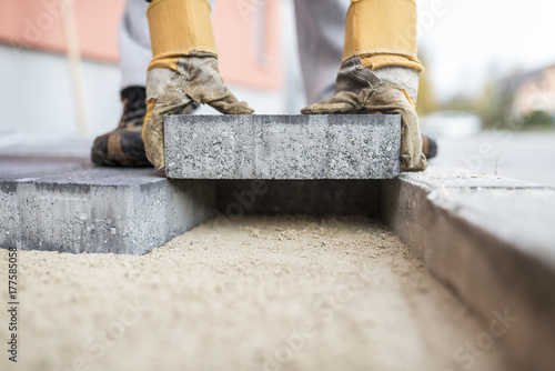 Builder laying outdoor paving slabs Fotobehang