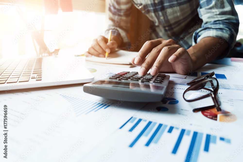 Fototapeta Close up of businessman or accountant hand holding pen working on calculator and laptop computer to calculate business data during make note at notepad, accountancy document at office